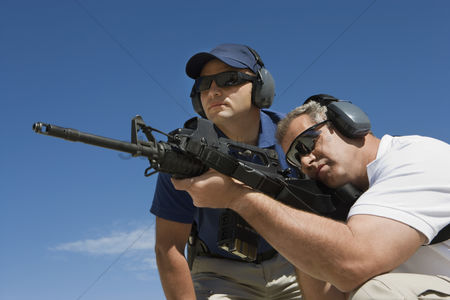 Firing : Instructor with man aiming machine gun at firing range low angle view