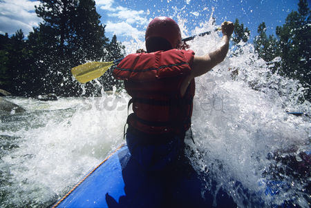 Arm raised : Kayaker paddling through rapids back view