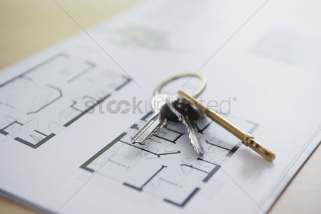 First : Key ring with three keys lying on architectural blueprint close-up