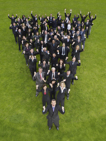Grass background : Large group of business people standing in triangle formation cheering elevated view