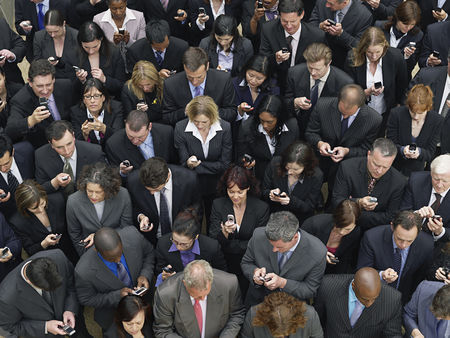 Cell phone : Large group of business people text messaging elevated view