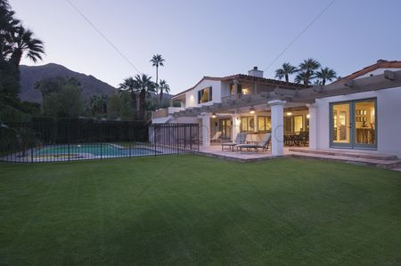 Grass : Lawn and swimming pool with lit exterior of palm springs home exterior
