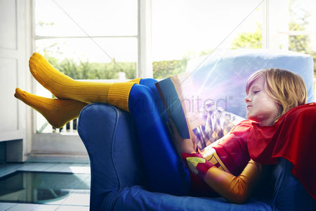 Smiling : Little boy dressed as a super hero reading a book