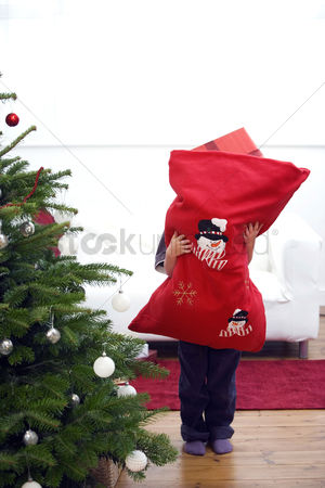 Comfy : Little boy hugging a bag full of gifts
