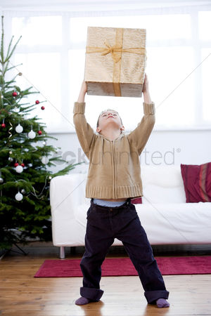 Comfy : Little boy lifting a present