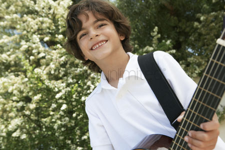 Children playing : Little boy playing guitar