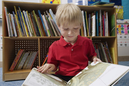 School children : Little boy reading a picture book