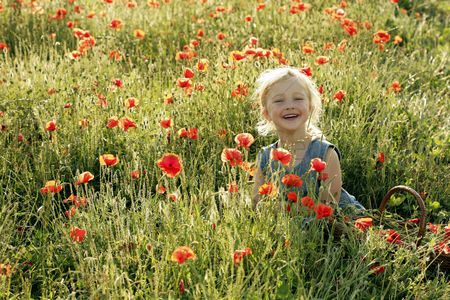 Grass : Little girl smiling in a field of flowers