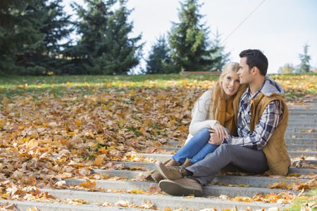 Steps : Loving couple hugging while sitting on steps in park during autumn