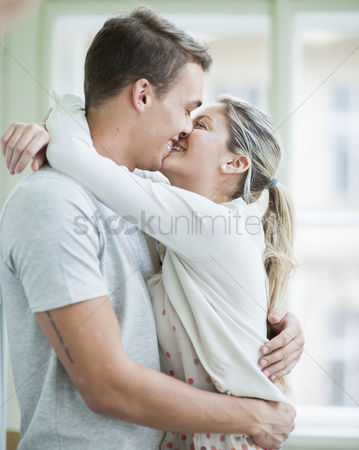 Kissing : Loving couple kissing while hugging in house
