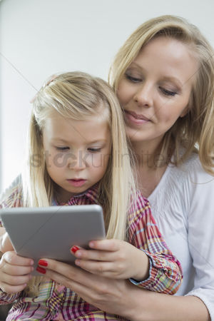 Sitting on lap : Loving woman with daughter using digital tablet at home
