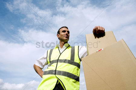 Strong : Low angle view of a delivery man beside some boxes