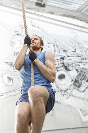 Rope : Low angle view of determined man climbing rope in crossfit gym