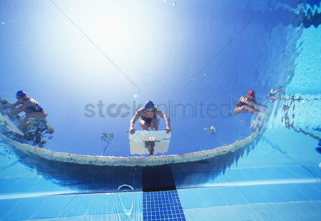 Diving : Low angle view of female swimmers ready to dive in pool from starting position
