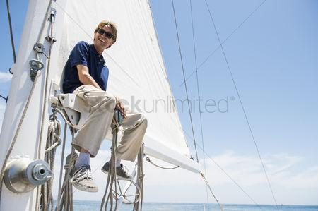 Rope : Low angle view of smiling man sitting on yacht boom