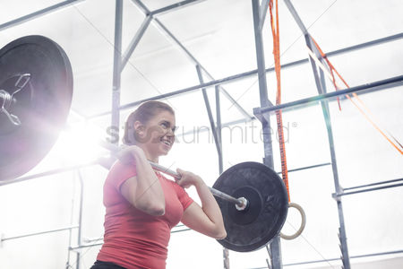Physical : Low angle view of smiling woman lifting barbell in crossfit gym