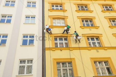 Czech republic : Low angle view of window washers hanging outside building