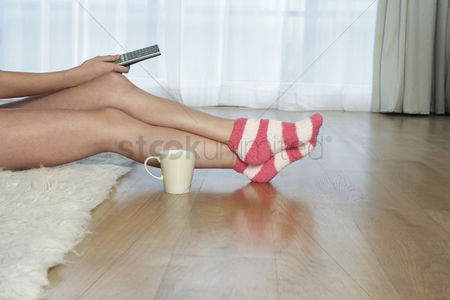 Indulgence : Low angle view of woman in stripey socks holding remote control