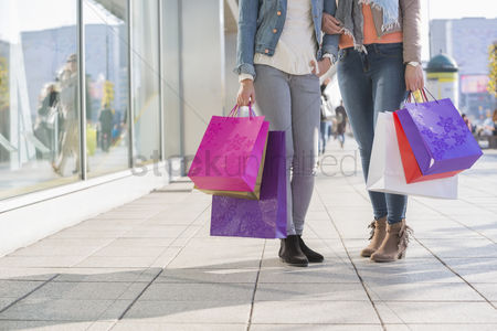 Two people : Low section of female friends holding shopping bags on sidewalk