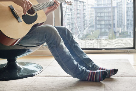 Furniture : Low section of man playing guitar