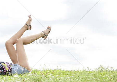 Grass : Low section of woman with feet up lying on grass against sky