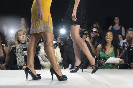 Fashion : Low section of women walking in black high heeled shoes on fashion catwalk
