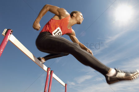 Fitness : Male athlete jumping hurdle mid air