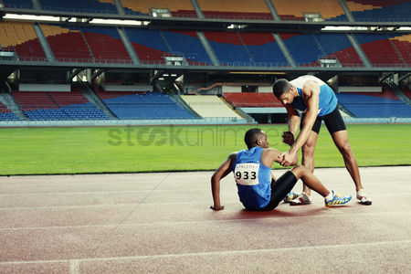 Pain : Male athlete laying on track  clasping leg in pain  another athlete helping