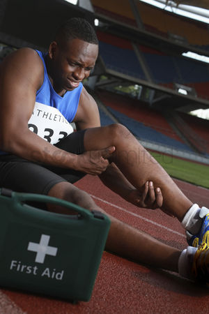 Pain : Male athlete lying on track  clasping leg in pain