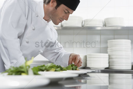 Appearance : Male chef preparing salad in kitchen