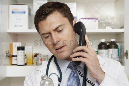 Medication : Male doctor using phone in hospital