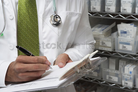 Medication : Male doctor writing in patient chart mid section