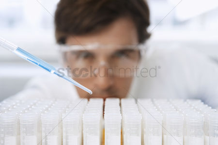 One man only : Male lab worker adding drops to test tubes
