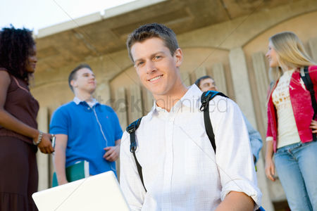 High school : Male student using laptop outdoors  portrait