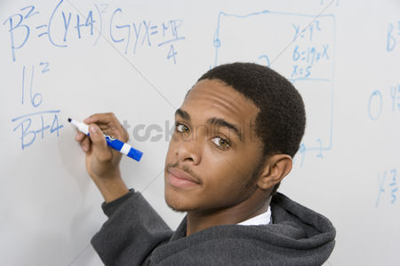 University : Male student writing maths equations on whiteboard
