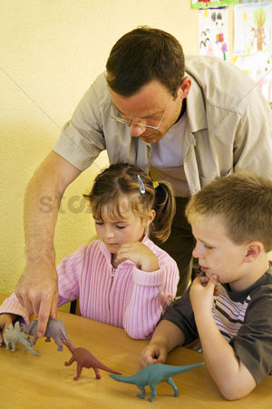 Teacher : Male teacher showing his students some dinosaur figurines