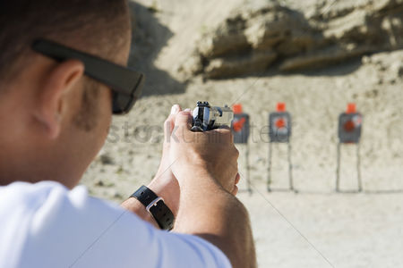 Firing : Man aiming hand gun at firing range
