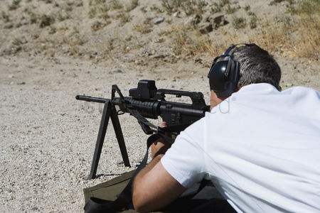 Firing : Man aiming machine gun at firing range