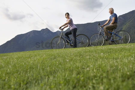 British ethnicity : Man and woman biking mountain range in background