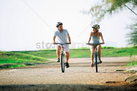 Eastern european ethnicity : Man and woman cycling in the park