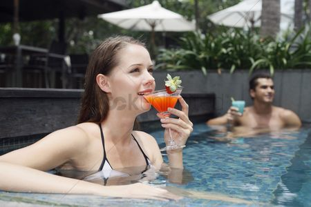 Eastern european ethnicity : Man and woman drinking while relaxing in the pool