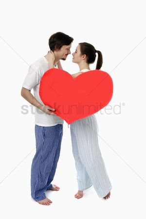 Kissing : Man and woman embracing  man holding a heart shaped cushion