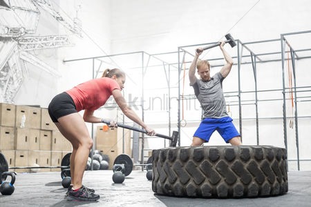 Fitness : Man and woman hitting tire with sledgehammer in crossfit gym