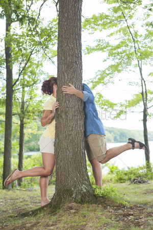 Kissing : Man and woman kissing behind tree in nature