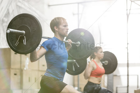 Three quarter length : Man and woman lifting barbells in crossfit gym