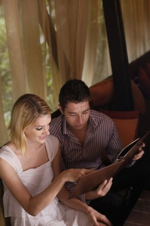 Choosing : Man and woman reading menu in a cafe