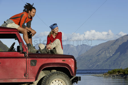 Transportation : Man and woman sitting on top of jeep near mountain lake