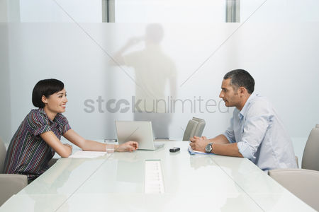 Office worker : Man and woman talk over conference table man on mobile phone visible through translucent office wall