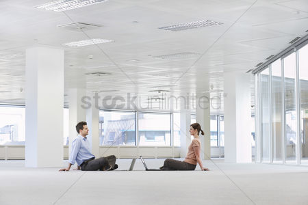 Sitting on lap : Man and woman with laptops in empty office space
