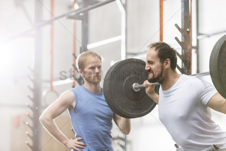 Muscle training : Man assisting friend in lifting barbell at crossfit gym